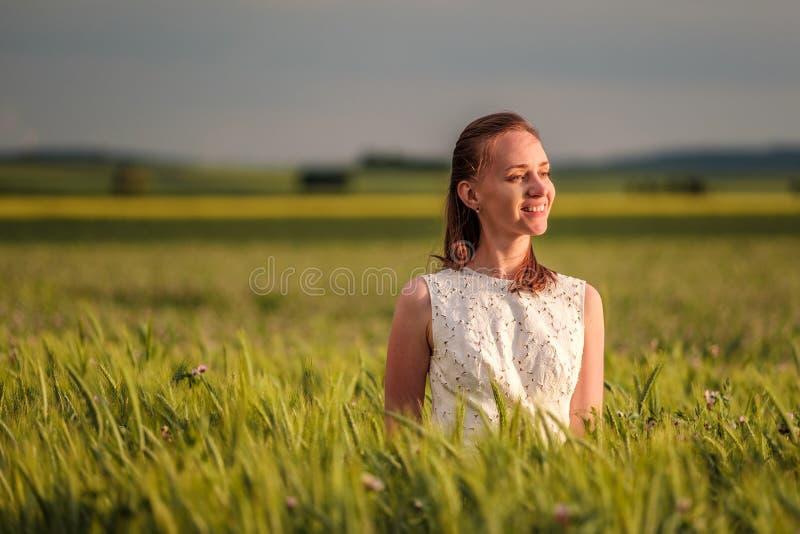 白色礼服的美丽的妇女在绿色麦田 免版税库存照片