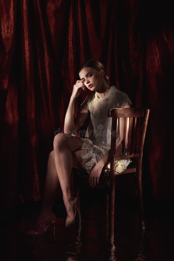 白色礼服的美丽的妇女在黑暗的伯根地背景 免版税库存照片