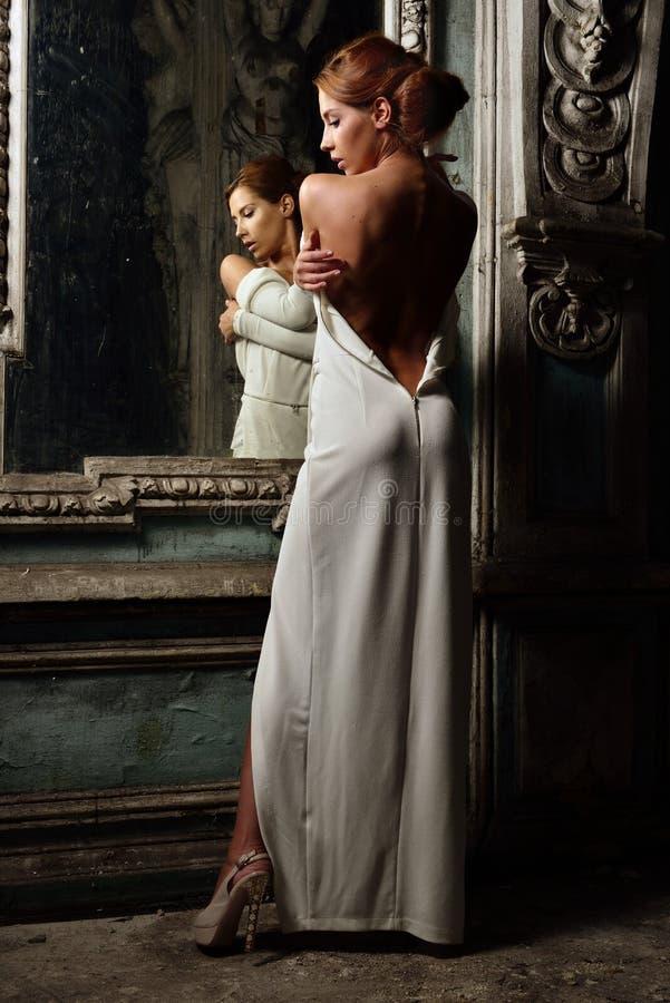 白色礼服的美丽的妇女有赤裸后面的。 免版税库存图片