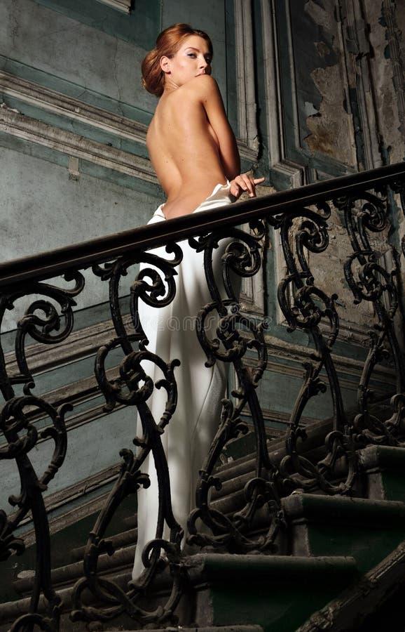 白色礼服的美丽的妇女有赤裸后面的在宫殿。 库存图片