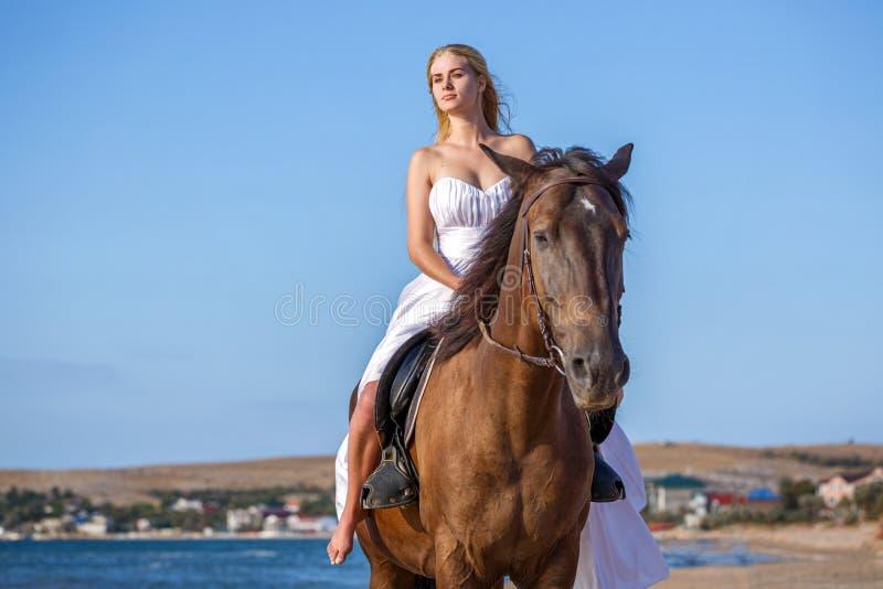 白色礼服的美丽的少妇由有马的海 免版税库存图片