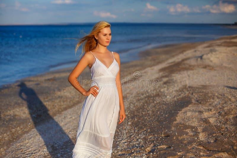 白色礼服的美丽的年轻女人由海在阳光下 库存照片