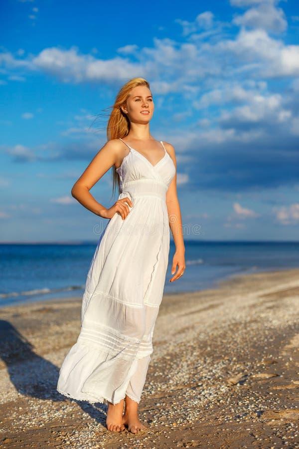 白色礼服的美丽的年轻女人由海在阳光下 免版税库存图片
