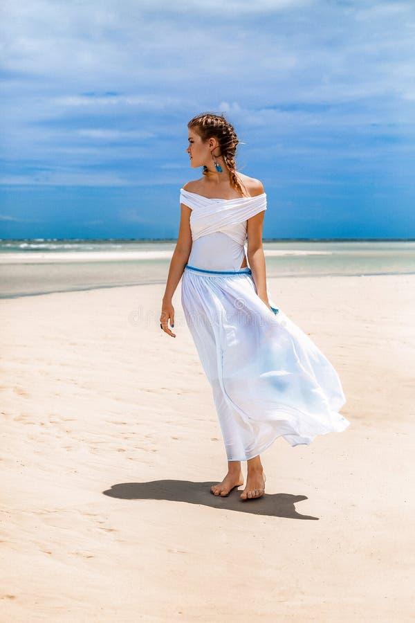 白色礼服的美丽的年轻时髦的女人在海滩 免版税库存照片
