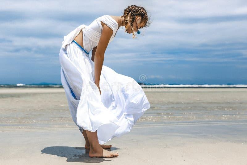 白色礼服的美丽的年轻时髦的女人走由的 免版税库存图片