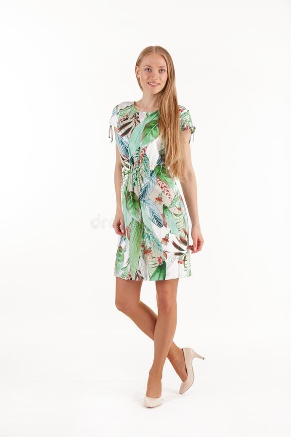 白色礼服的美丽的年轻白肤金发的妇女有在白色背景隔绝的热带印刷品的 库存照片