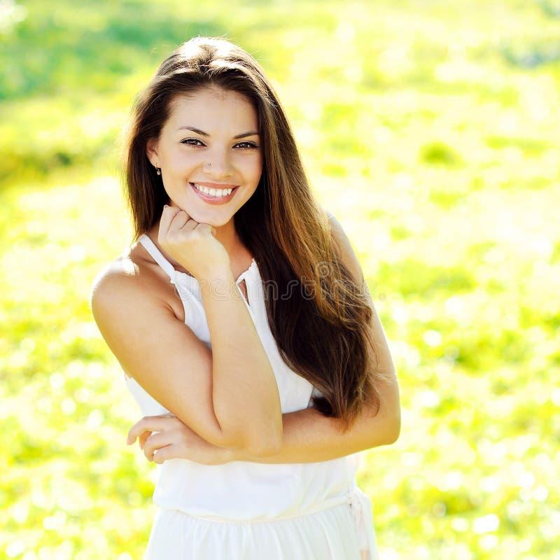 白色礼服的美丽的微笑的女孩夏令时 免版税库存照片