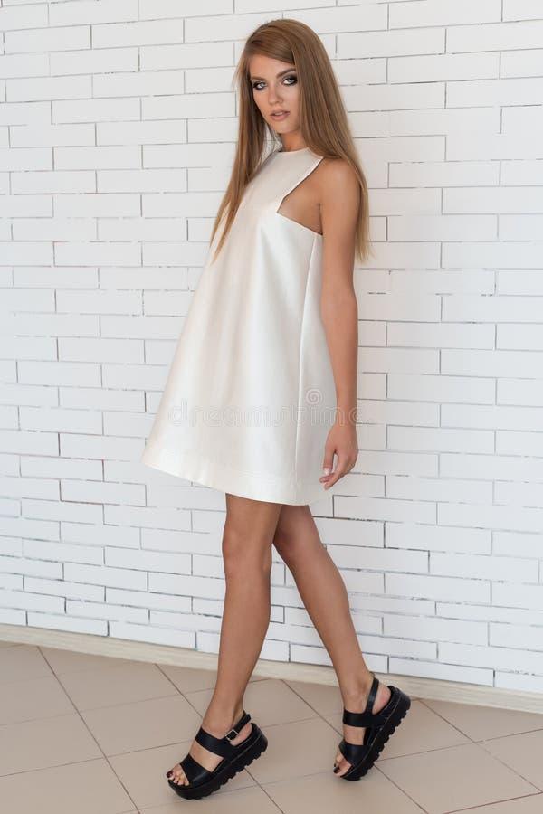 白色礼服的美丽的性感的大胆的时兴的女孩在摆在一个白色砖墙附近的时髦黑鞋子在演播室 免版税图库摄影