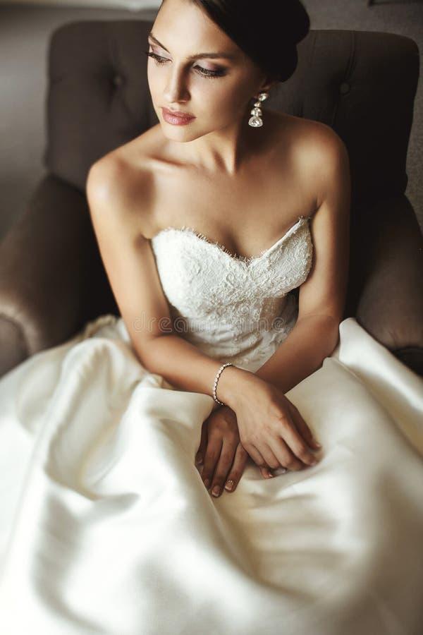 白色礼服的美丽的肉欲的深色的新娘坐leath 免版税库存照片