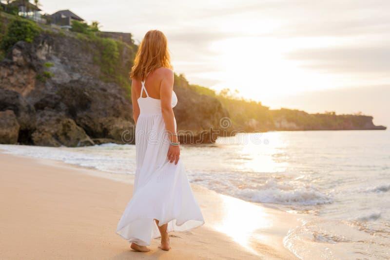 白色礼服的轻松的妇女走在海滩的在晚上 免版税库存照片