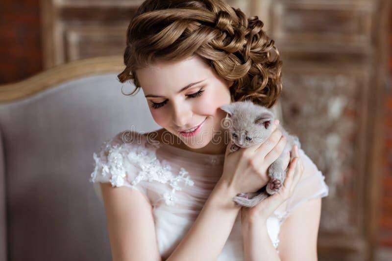 白色礼服的迷人和美丽的女孩坐长沙发 库存照片