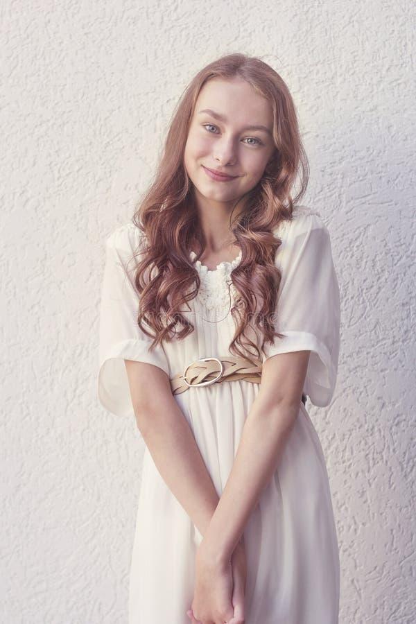 白色礼服的逗人喜爱的微笑的女孩 图库摄影