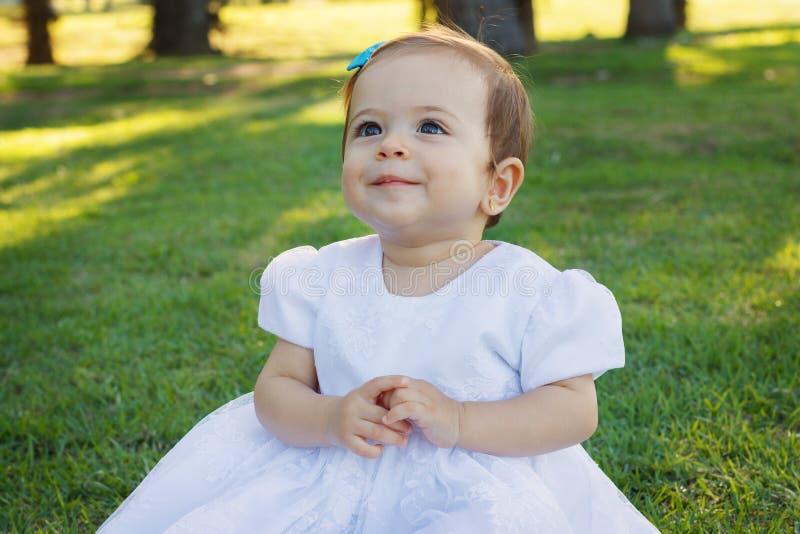 白色礼服的逗人喜爱的愉快的矮小的微笑的女婴 免版税库存照片
