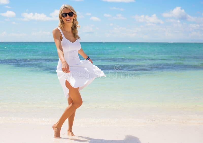 白色礼服的年轻愉快的妇女在海滩 免版税图库摄影