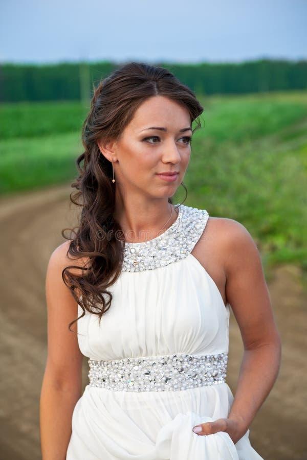 白色礼服的年轻美丽的妇女在自然 库存照片