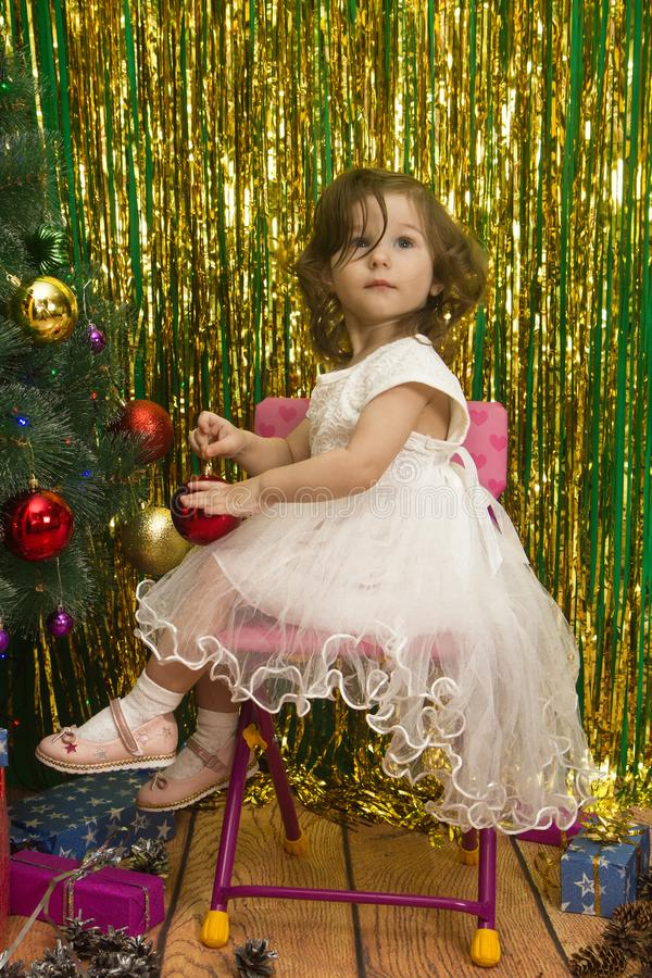 白色礼服装饰圣诞树的愉快的女孩 免版税库存图片