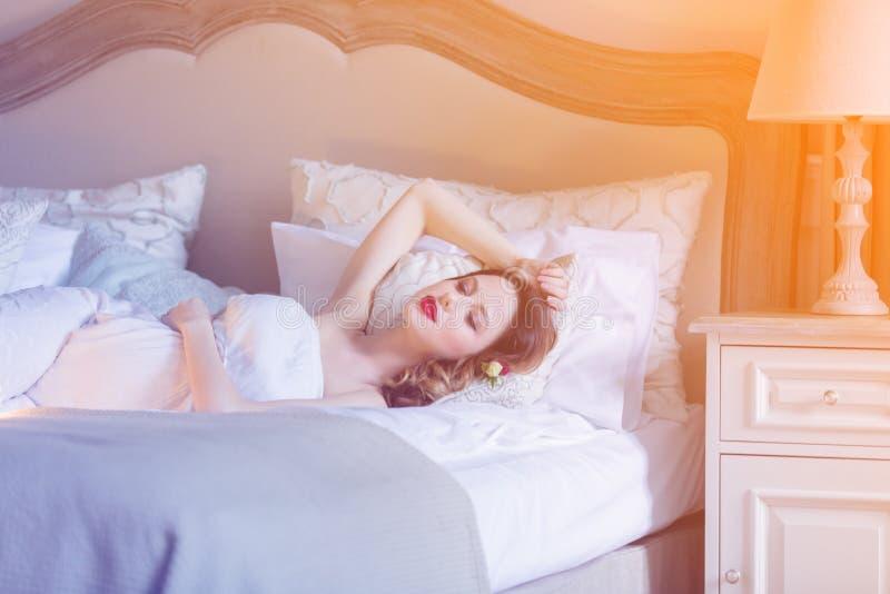 白色礼服说谎的dowm的年轻人孕妇在床上 免版税库存图片