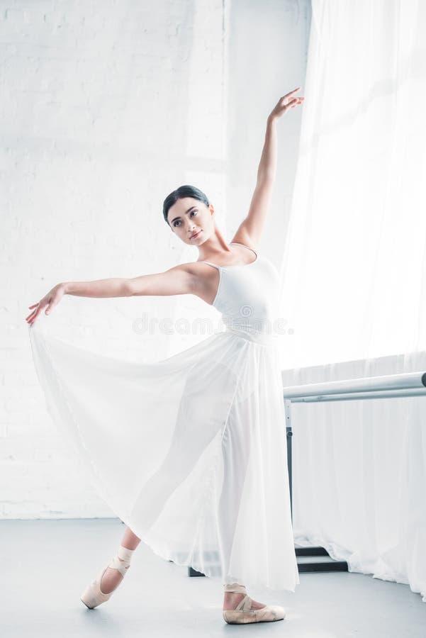 白色礼服跳舞的典雅的年轻芭蕾舞女演员 免版税库存图片