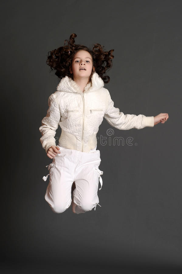 白色礼服跳跃的女孩 免版税库存图片