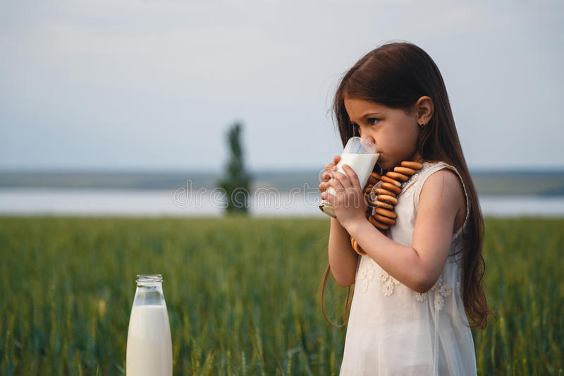 白色礼服饮用奶的愉快的小女孩在一个绿色领域 免版税库存照片