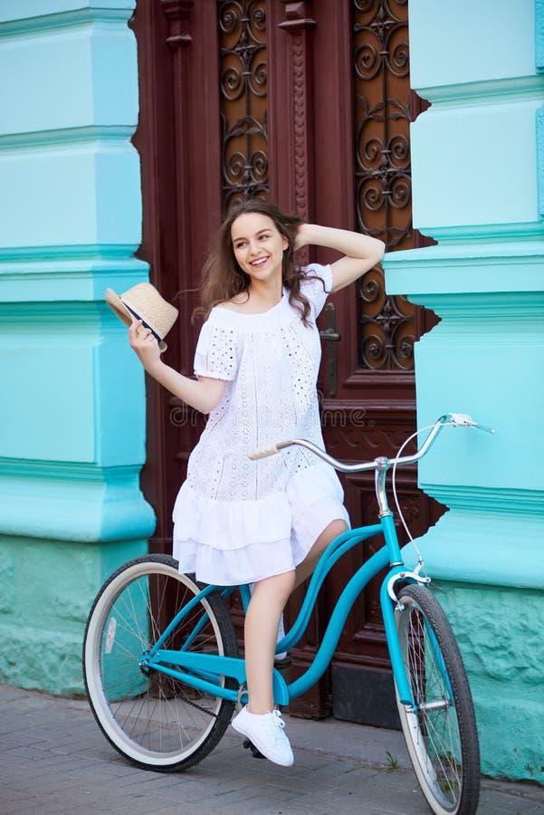 白色礼服骑马葡萄酒蓝色自行车的微笑的俏丽的女孩在与古色古香的红色门的美丽的老蓝色大厦附近 免版税图库摄影