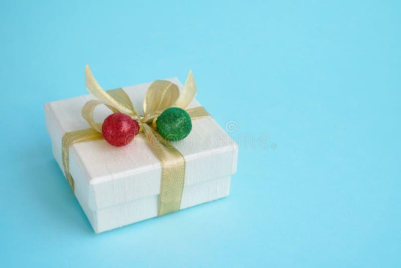 白色礼物或当前boh与圣诞节装饰在蓝色后面 库存图片