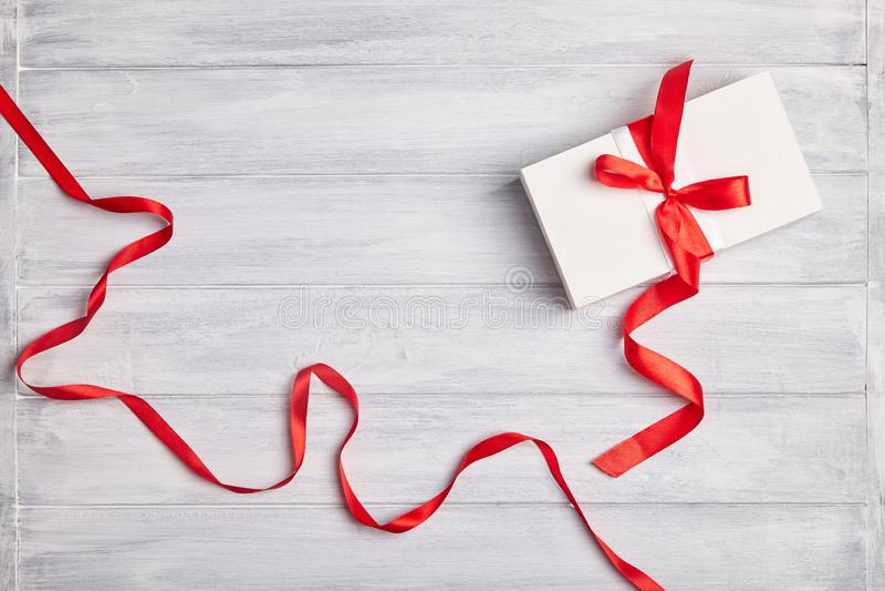 白色礼物盒包裹与在木背景的红色丝带 库存图片