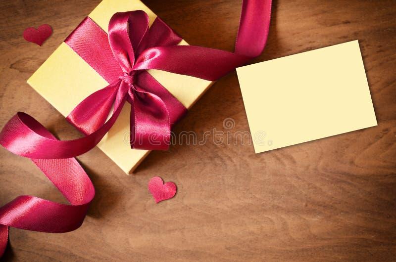 白色礼物盒和红色丝带与标记在木背景 葡萄酒在木板的礼物盒有文本的空间的 库存图片