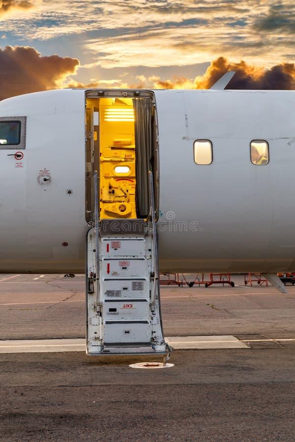 白色私人喷气式飞机和开放梯子在机场以剧烈的天空和日落为背景 免版税库存图片