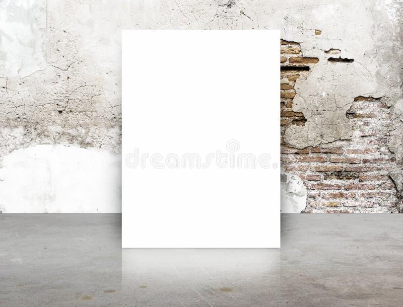 白色空白的海报在高明的砖墙和具体地板室, T 免版税库存图片