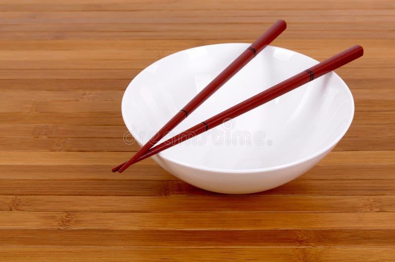 白色空的饭碗木筷子竹子背景 免版税库存照片