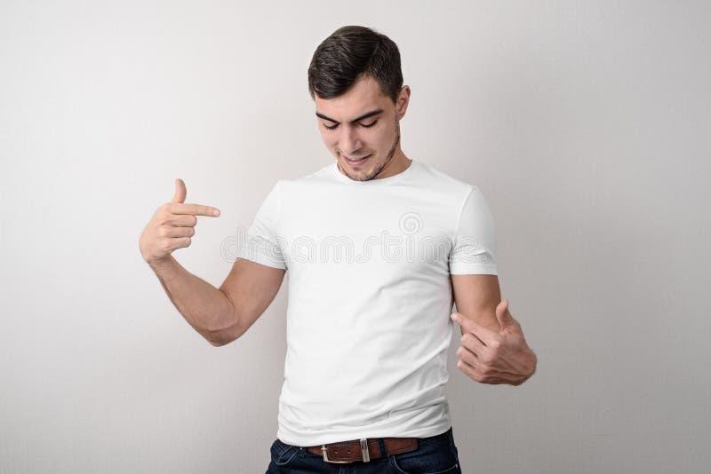 白色空的T恤杉的年轻人显示她的手指、地方设计的或布局 免版税库存照片