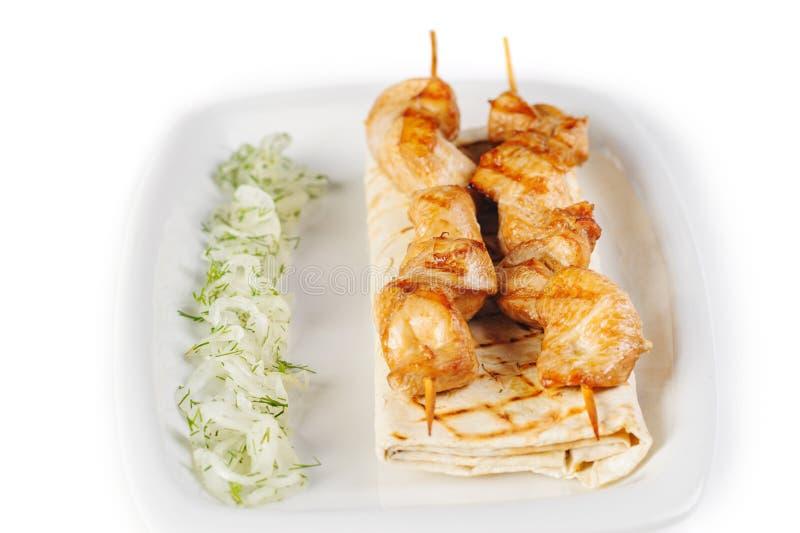 白色突显背景中的白盘上,烤肉串上的烤肉串,上面有草灰、洋葱和青菜 免版税库存图片