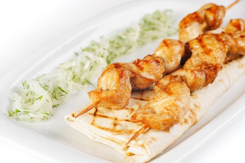 白色突显背景中的白盘上,烤肉串上的烤肉串,上面有草灰、洋葱和青菜 库存照片