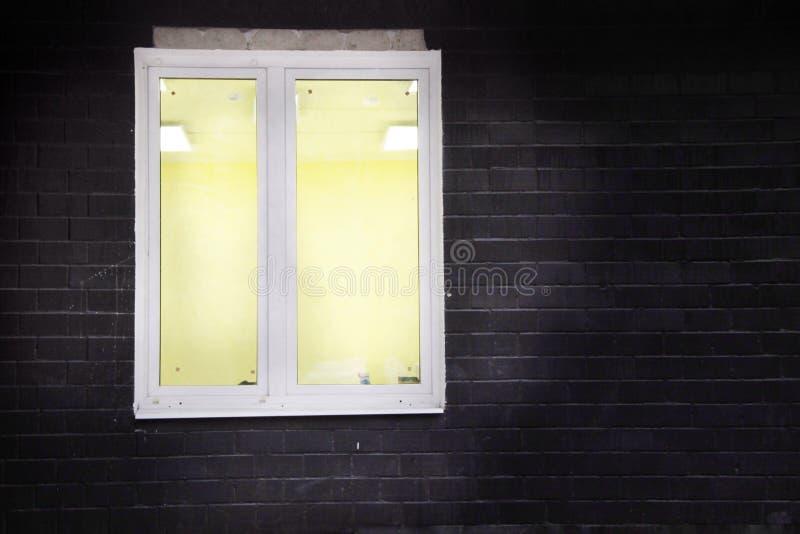 白色窗架,在窗口里面的黄灯,在一个黑砖墙上 库存图片