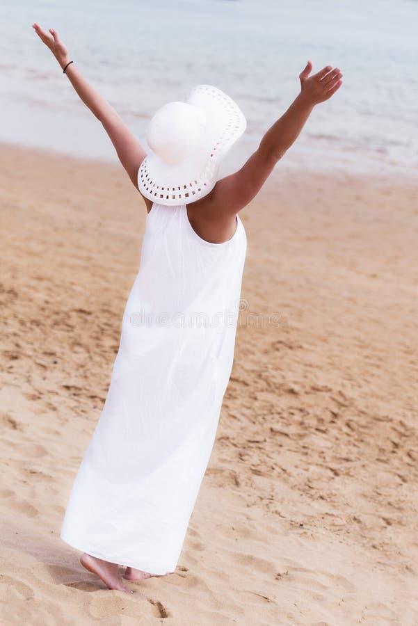 白色站立在与ha的一个海滩的帽子和礼服的赤足女孩 免版税库存图片