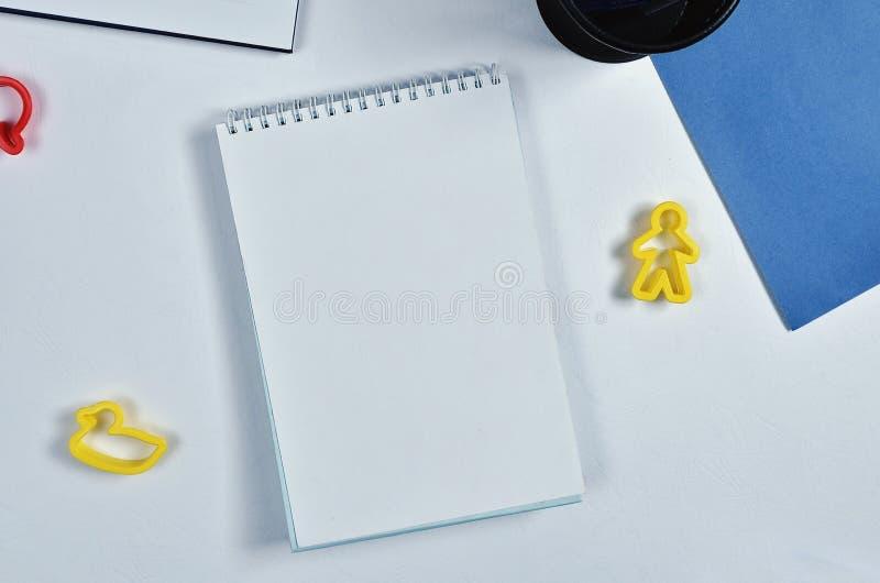 白色笔记本、蓝纸、笔和笔匣,在白皮书背景 库存照片