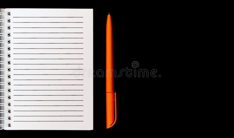 白色笔记本和橙色笔在被隔绝的黑背景顶视图 库存图片