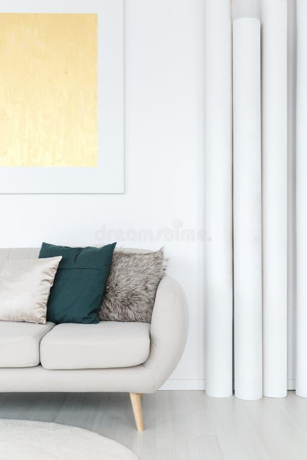 白色管临近灰色沙发 免版税库存图片