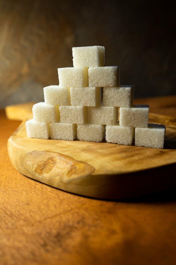 白色粗制糖立方体在木背景的与在一个切板的光反射由橄榄色的木头制成 免版税库存图片