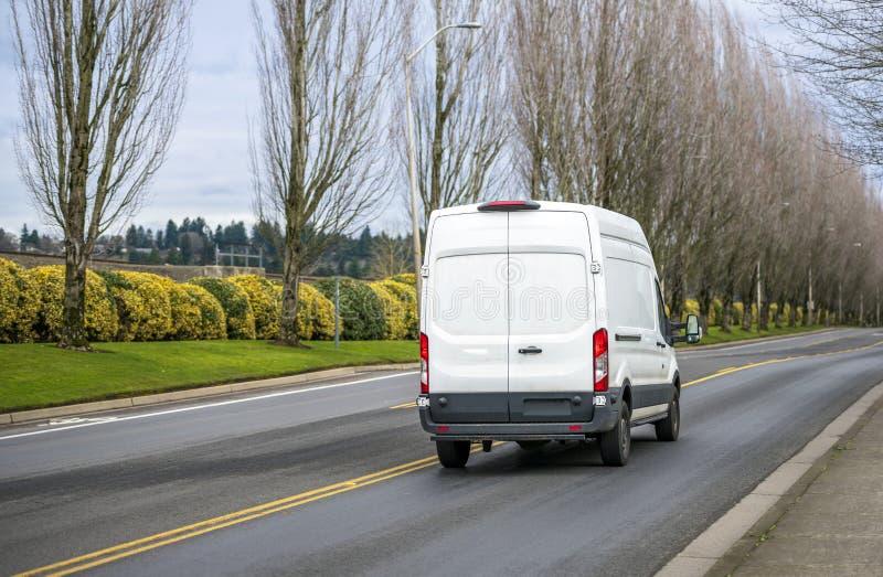 白色紧凑商业运行在有树胡同的路的货物微型搬运车 免版税库存照片