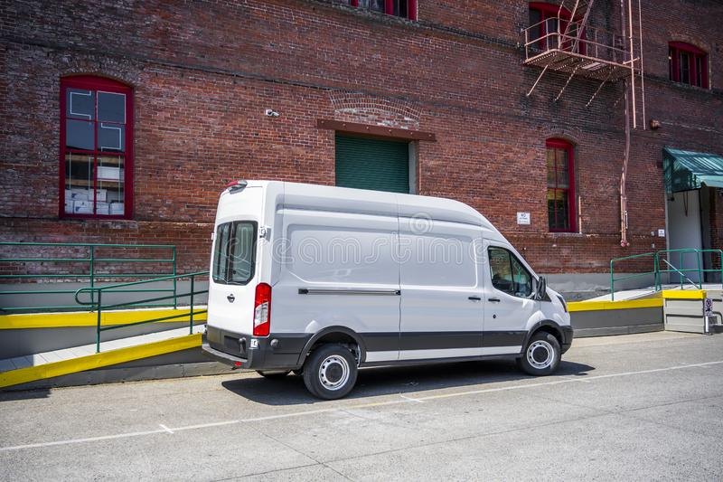 白色紧凑普遍的地方交付和企业身分的货物微型搬运车在仓库停车场 免版税图库摄影