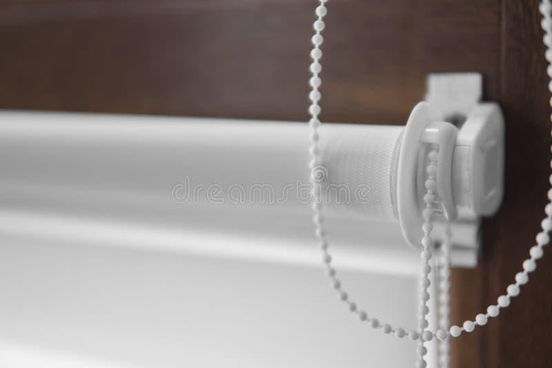 白色织品路辗窗帘细节在塑料窗口的与木纹理在客厅 免版税库存照片
