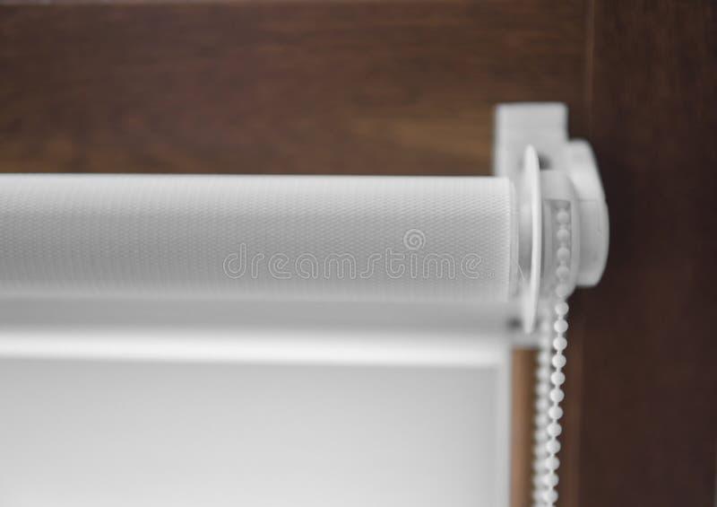 白色织品路辗窗帘细节在塑料窗口的与木纹理在客厅 免版税库存图片