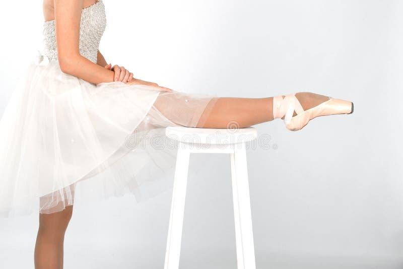 白色经典礼服和pointe的芭蕾舞女演员舒展 免版税库存照片