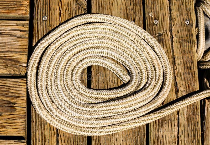 白色绳索卷在木码头的 库存图片