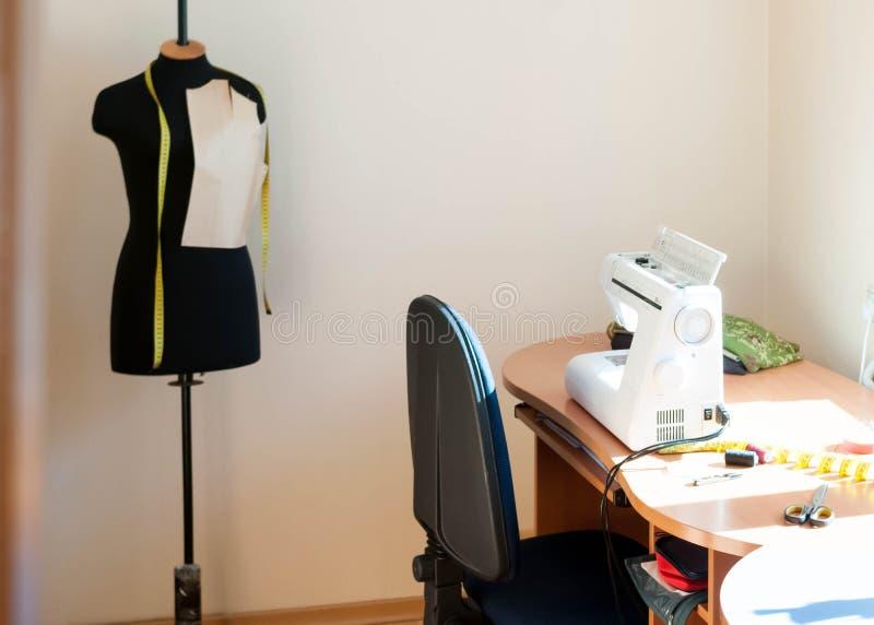 白色缝纫机,蓝色椅子,与磁带的黑时装模特 免版税图库摄影