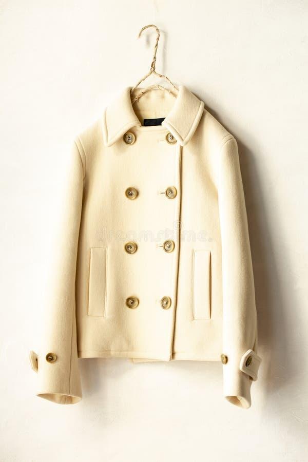 白色羊毛涂上垂悬在白色背景的晒衣架 免版税图库摄影
