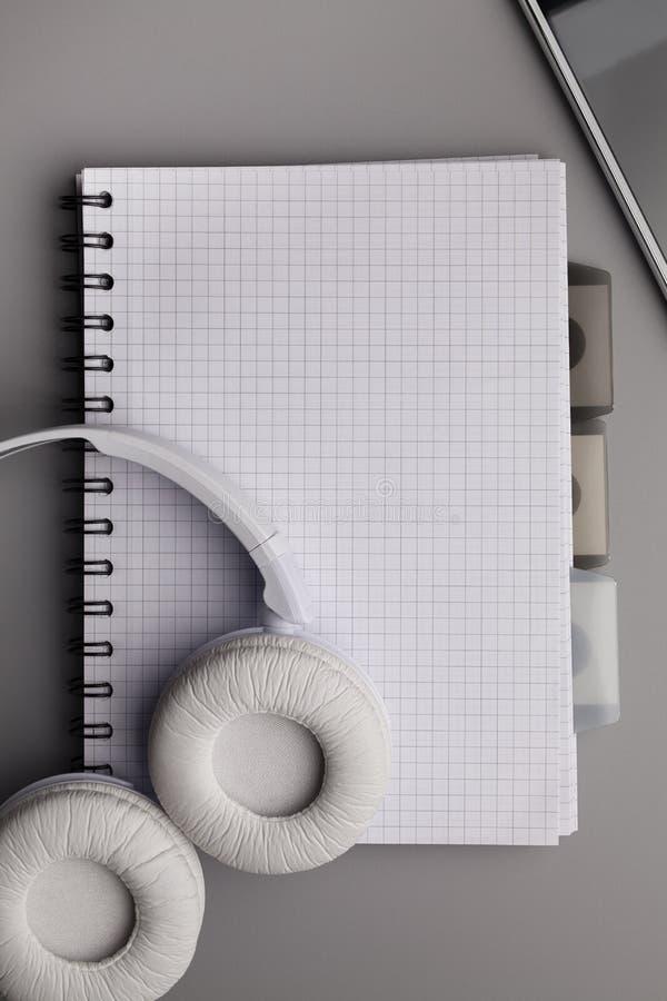 白色耳机和笔记本有空白页的在灰色桌上 库存图片