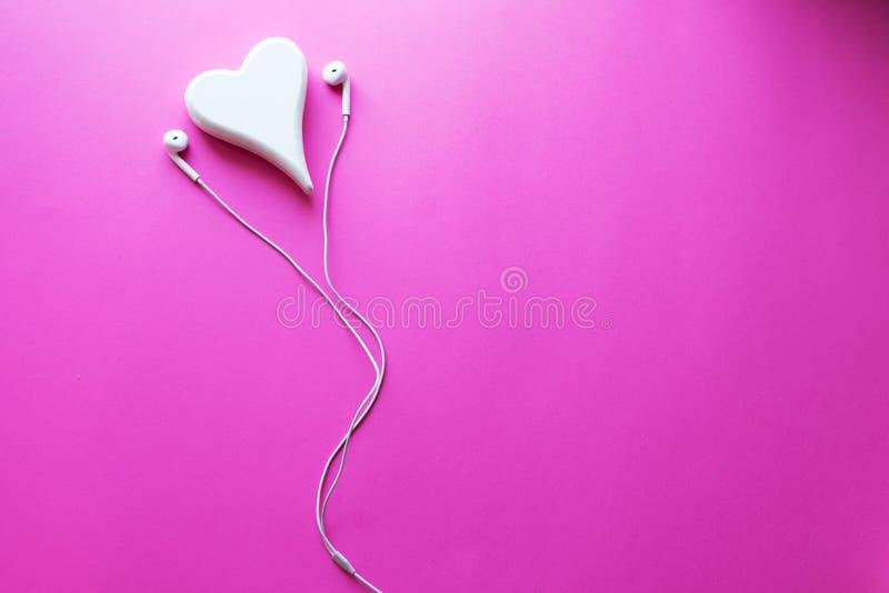 白色耳机顶视图可爱的特写镜头在桃红色淡色塑料纹理背景的 淡色概念,最小的概念 免版税图库摄影